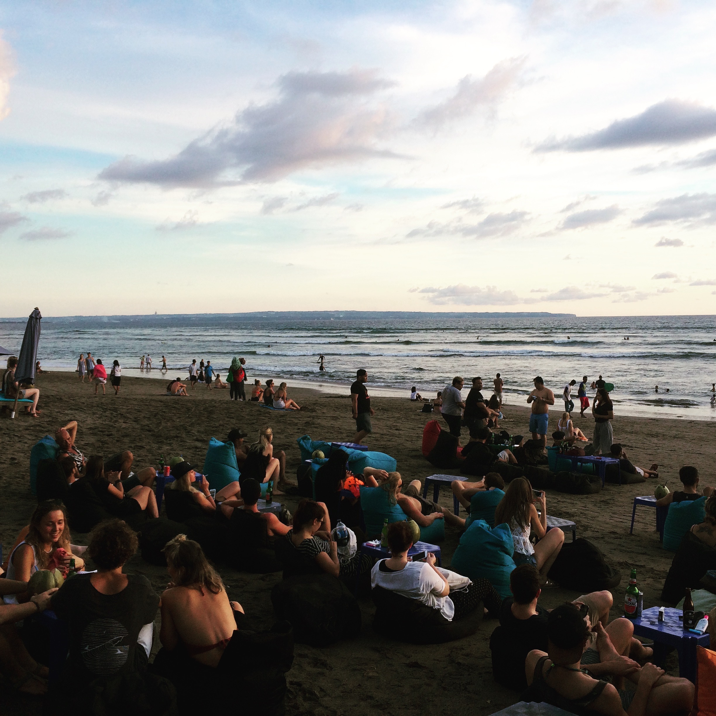 People sitting on bean bags and drinking on the beach. They are waiting for the sunset in Bali.